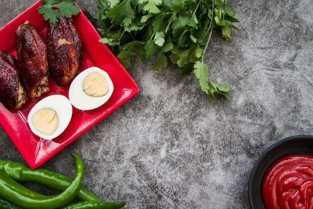 Grilled chicken breasts with boiled egg and ingredients on concrete background