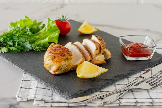 Grilled chicken breasts with vegetables served on a stone with lemon and tomato sauce.