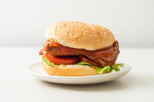 白い皿にソースをかけたチキンバーガーのグリル