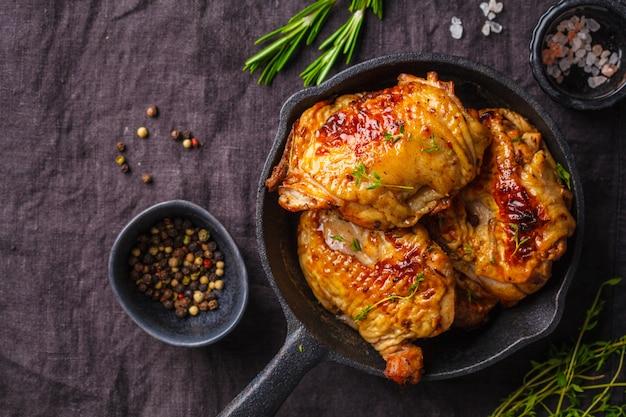 Grilled chicken  in a cast iron skillet, top view, dark background.
