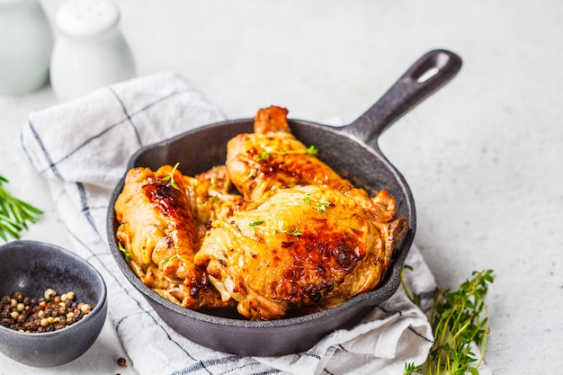 Grilled chicken  in a cast iron skillet, white background.