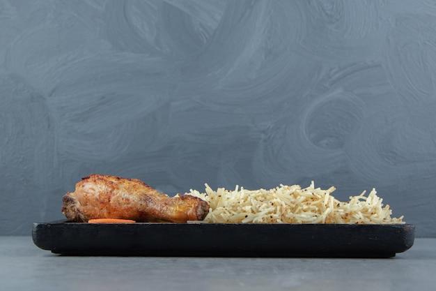 Жареный цыпленок, куриная ножка и макароны на черной тарелке.