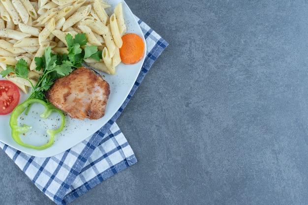 Pollo alla griglia e penne cremose sul piatto bianco.