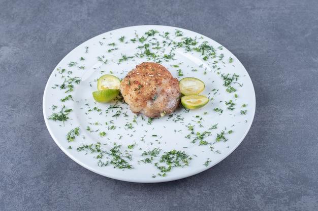 Pollo alla griglia decorato con verdure su piatto bianco.