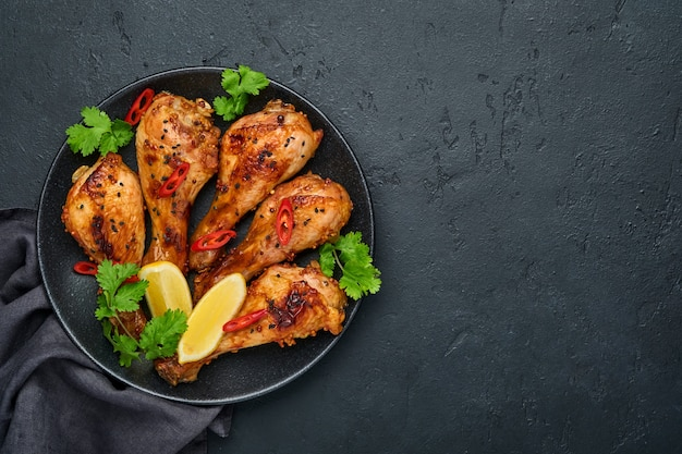 Жареные куриные голени или ножки или жареный барбекю со специями и томатным соусом сальса на черной тарелке. вид сверху с копией пространства.