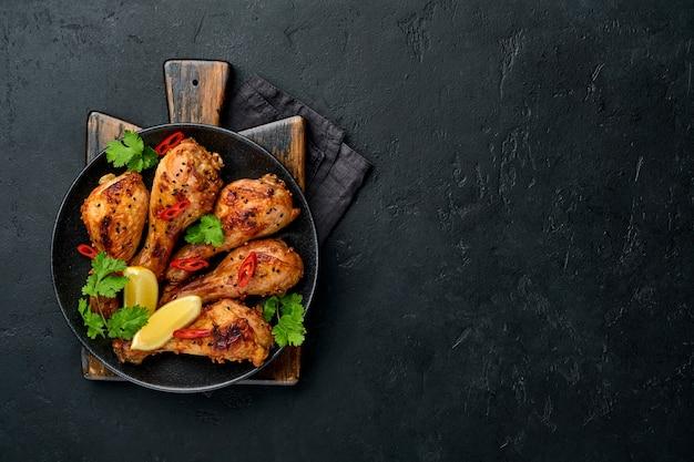 Жареные куриные голени или ножки или жареный барбекю со специями и томатным соусом сальса на черной тарелке. вид сверху