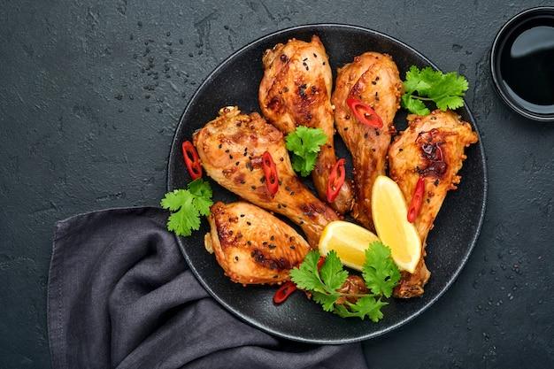 Куриные голени или ножки на гриле или жареный барбекю со специями и томатным соусом сальса на черной тарелке