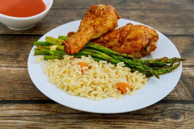 鶏のモモ肉のグリル、ご飯、アスパラガス、バッファローソース添え。