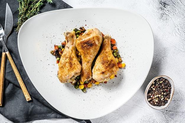 白い皿に野菜を添えた鶏のモモ肉のグリル。白色の背景。