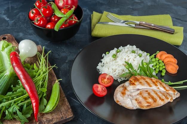 Куриное филе гриль и отварной рис на темной тарелке, украсить из разных овощей