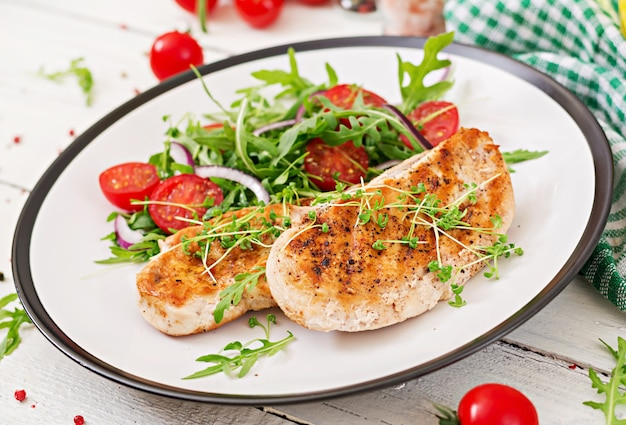 鶏ムネ肉のグリル、トマト、赤玉ねぎ、ルッコラの野菜サラダ。鶏肉のサラダ。健康食品。