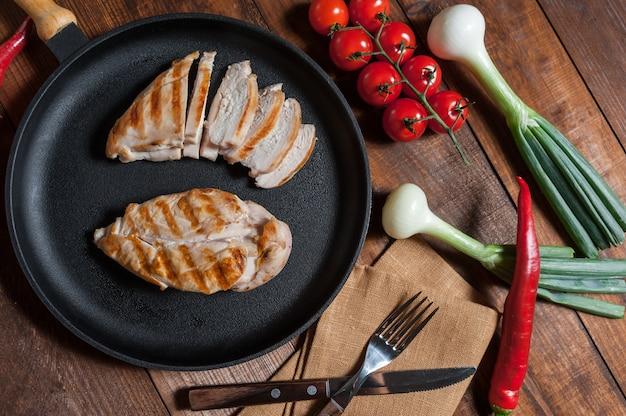 Куриное филе гриль на сковороде. сырые овощи в миске, деревянный стол