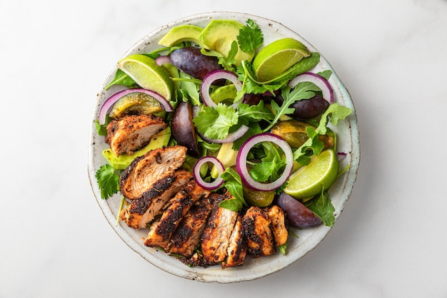 Салат из куриного филе на гриле с рукколой, авокадо, сливами, луком и лаймом в тарелке на белом фоне. вид сверху