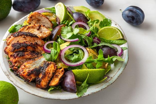 Салат из куриного филе на гриле с рукколой, авокадо, сливами, перцем, луком и лаймом в тарелке на белом фоне. крупным планом. здоровое диетическое питание