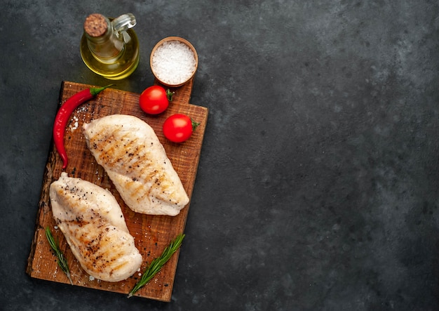 Grilled chicken fillet with spices on a stone background with copy space for your text