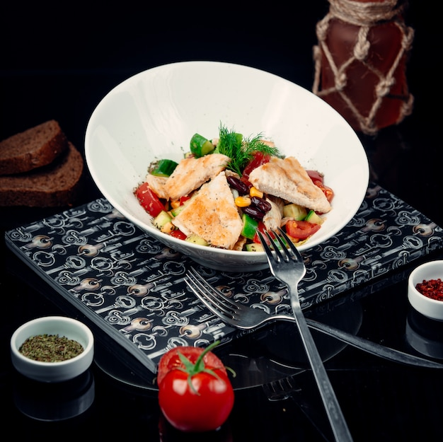 Grilled chicken fillet with vegetable salad in a white bowl.