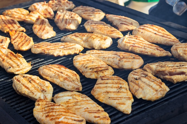 Grilled chicken fillets on the barbecue. street food.