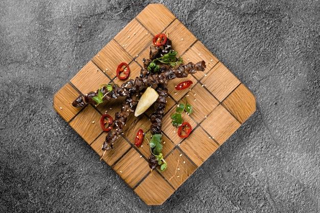 木製の串にライムを添えたチキンハートのグリル、灰色の表面に唐辛子、コリアンダー、ゴマを添えて。