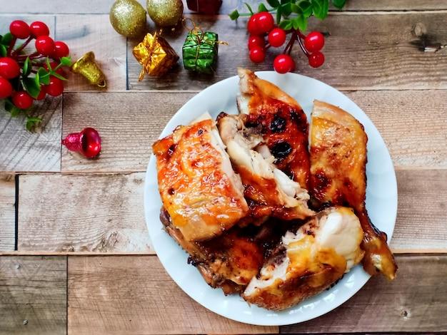 Курица-гриль в тарелке с украшениями и подарком на деревянном фоне