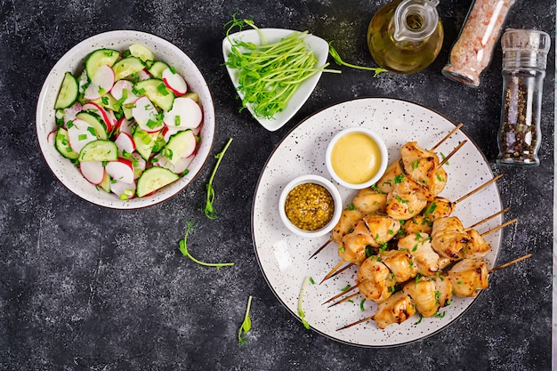 Grilled chicken kebab and salad with cucumber, radish, onion. top view