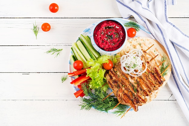 Grilled chicken kebab with beet hummus and pita, fresh vegetables on a white table