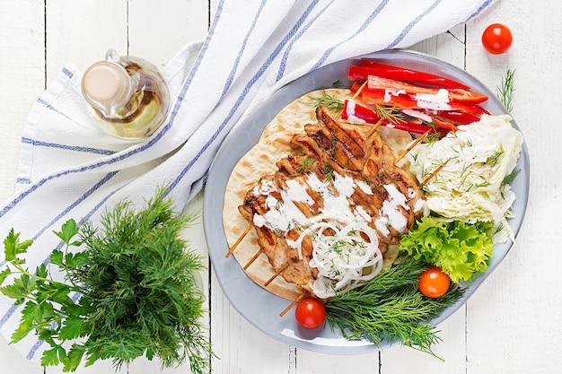 Куриный шашлык на гриле с лавашем, свежие овощи на белом столе
