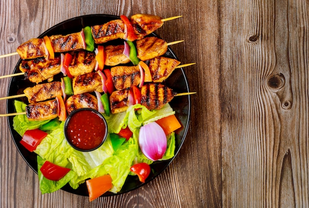 Grilled chicken kebab on wooden skewer with sauce