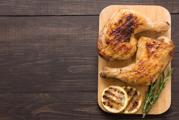 Grilled chicken lag and rosemary on wooden background