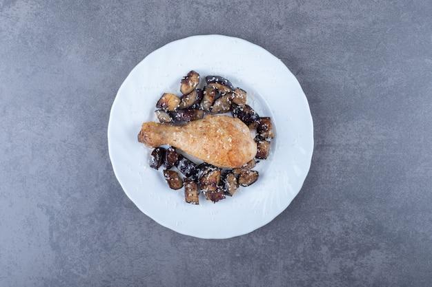 Жареная куриная ножка и баклажаны на белой тарелке.