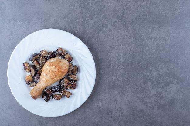 Coscia di pollo alla griglia e melanzane su piatto bianco.