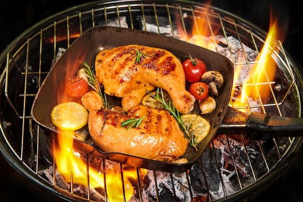 그릴 팬에 구운 닭 다리. 토마토, 레몬 슬라이스, 버섯, 로즈마리와 함께 제공되는 식욕을 돋우는 육즙이 가득한 구운 닭고기와 황금빛 갈색 크러스트. 선택적 초점. 건강한 식사 개념.