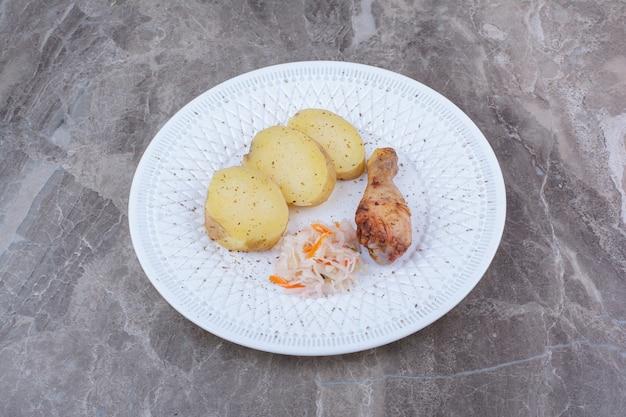 Grilled chicken leg, potato and sauerkraut on white plate.