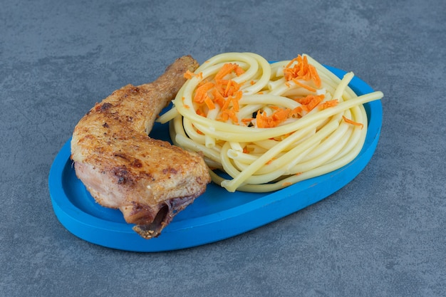 Grilled chicken leg and spaghetti on blue plate.