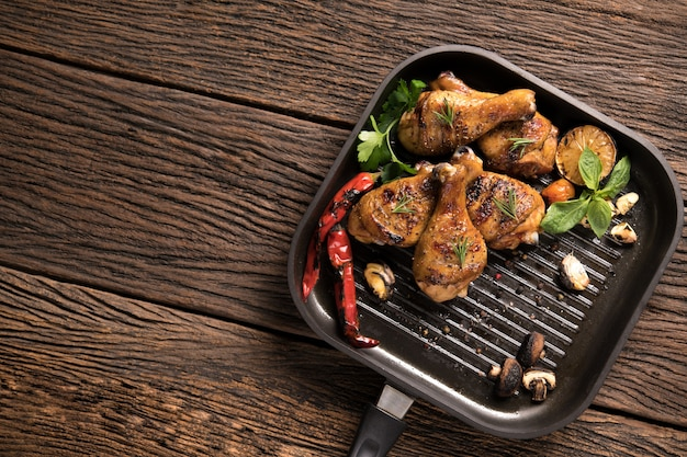 Grilled chicken leg with various vegetables on pan on old wooden background