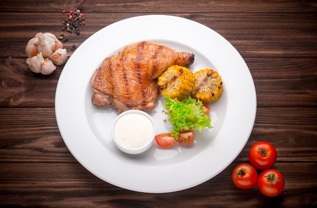 Grilled chicken leg with vegatables and seasoning on a wooden background