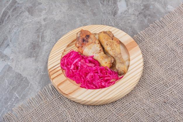 구운 닭 다리와 나무 접시에 절인 양배추.