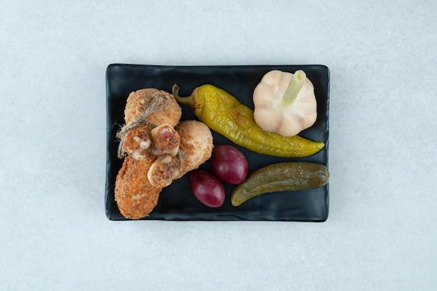 Жареные куриные ножки и маринованные овощи на черной тарелке.