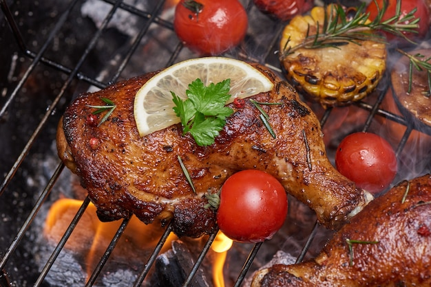 Grilled chicken legs on the flaming grill with grilled vegetables with tomatoes, potatoes, pepper seeds, salt.