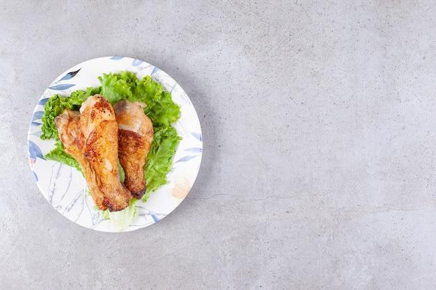 흰색 접시에 양상추와 구운 된 닭 다리 고기