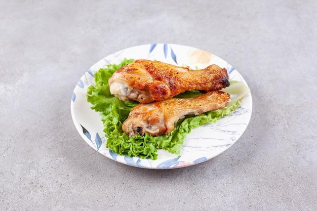 Carne di cosce di pollo alla griglia con lattuga sul piatto bianco