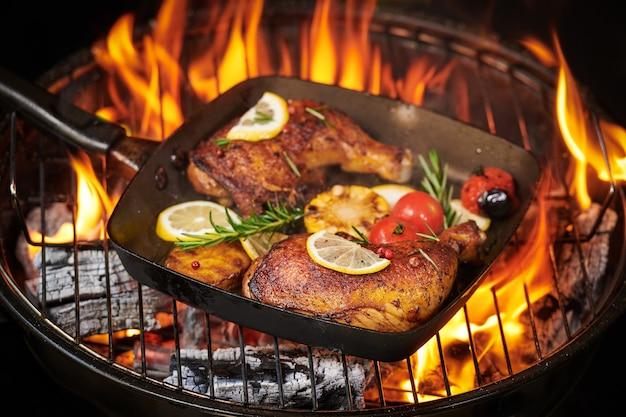 토마토, 감자, 고추 씨, 소금으로 구운 야채와 함께 불타는 그릴에 구운 닭 다리.