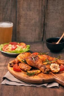 木製のまな板のグリルでローストした鶏の脚のグリル、ボウルにトマトソース、フレッシュトマトとレタスの葉、苦いコショウ、ビールのガラスマグ