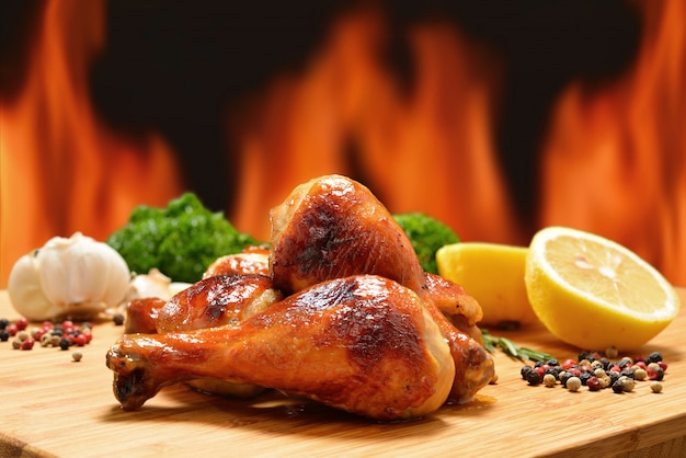 Grilled chicken legs and various vegetables on a chopping wood