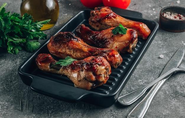 검정 잉크 판에 향신료와 구운 닭 다리