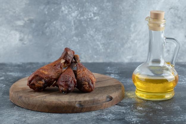 Cosce di pollo alla griglia su tavola di legno con un bicchiere di olio su sfondo grigio.