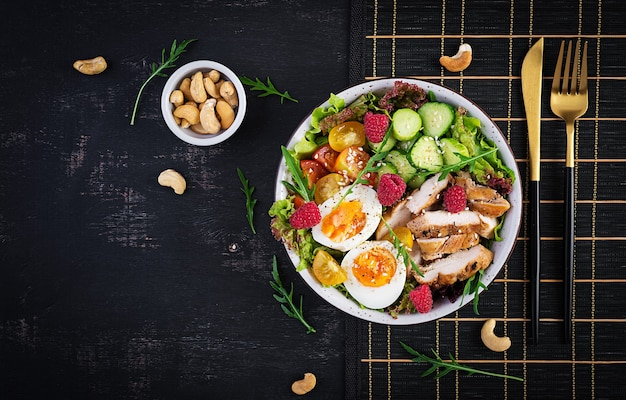 Куриное мясо на гриле и салат из свежих овощей из помидоров, огурцов, яиц, листьев салата и малины. кетогенная диета. блюдо чаши будды на темном фоне. вид сверху, плоская планировка
