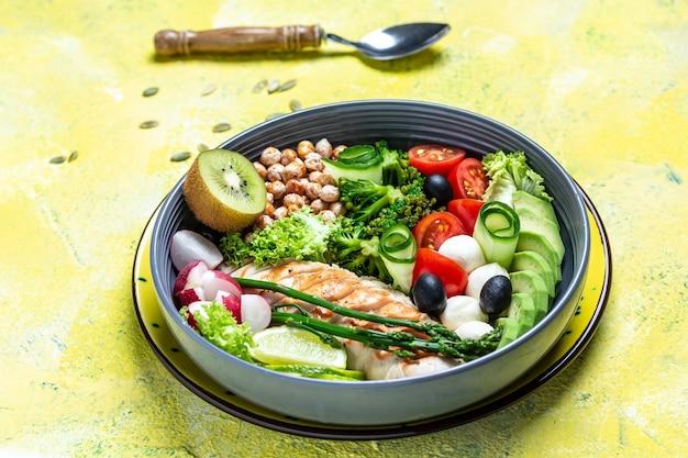 グリルした鶏肉と黄色の背景に新鮮な野菜のサラダ。健康的でデトックス食品のコンセプト。ケトジェニックダイエット。ブッダボウル料理、料理レシピの背景。クローズアップ、上面図、