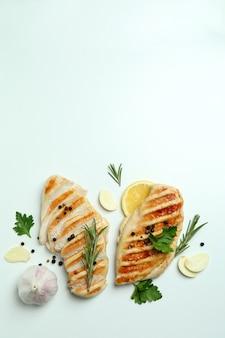 carne di pollo alla griglia e spezie su sfondo bianco