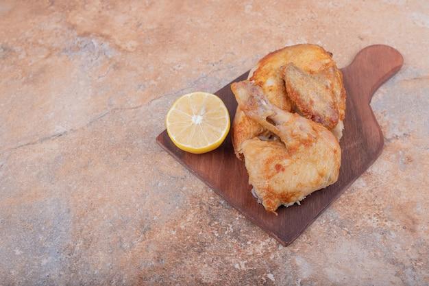 Carne di pollo alla griglia con limone su un piatto di legno
