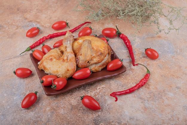 Carne di pollo alla griglia con peperoncino rosso e pomodori